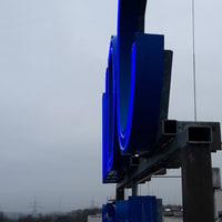 Beispiel Neonreklame-MDC- blau leuchtendes Filterglas-schraege Ansicht einer Dachwerbeschrift