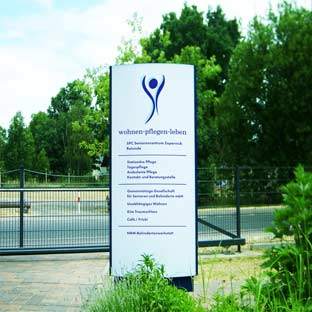 konvex gebogener Werbepylon, unbeleuchet, blaue Schriften auf weissem Hintergrund